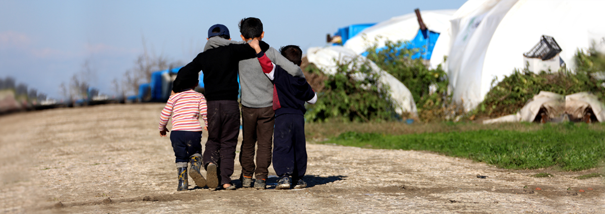Image of migrant children arm in arm in a refugee camp