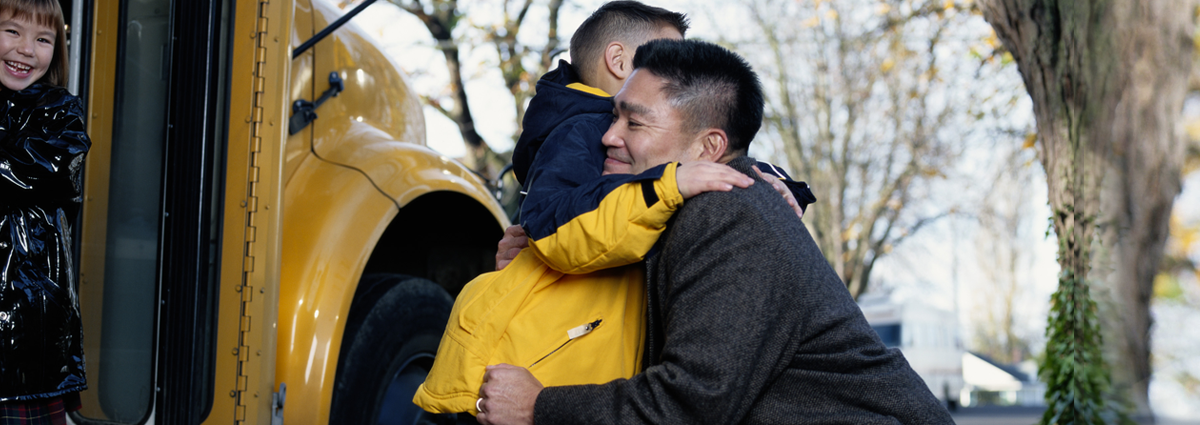 Image of father hugging young son in front of a schoolbus