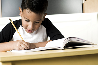 Young Hispanic student writing in a notebook