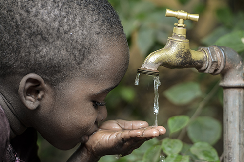 African boy drinking water from a pump