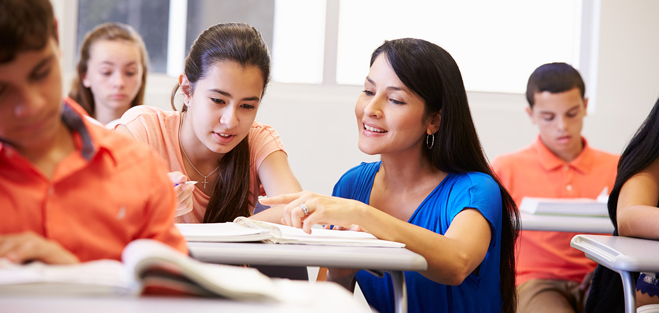 Image of Hispanic teacher and teen student in a classroom