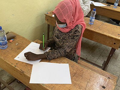 Image of Ethiopian child studying and wearing a mask