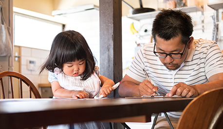 Image of father and young daughter reading together