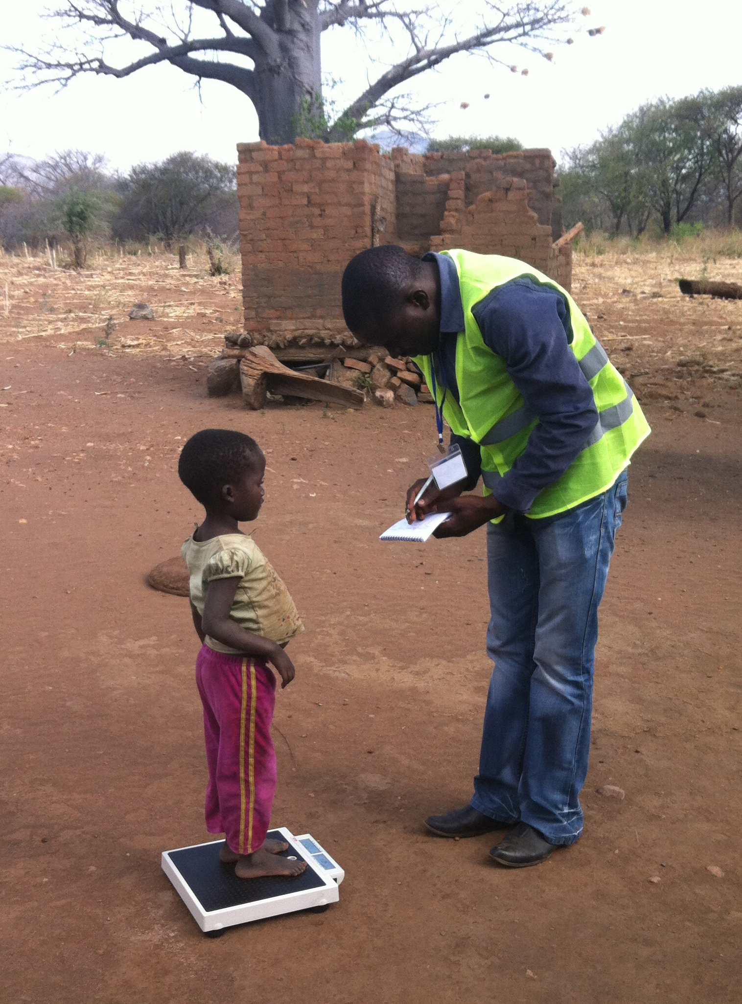 Man weighing child in Zimbabwe