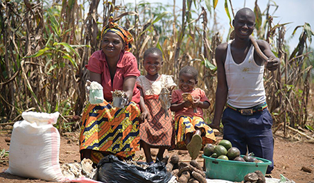 Image of young family in Africa with root vegetables