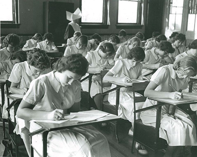 Image of students from the 1960s taking a test in a classroom