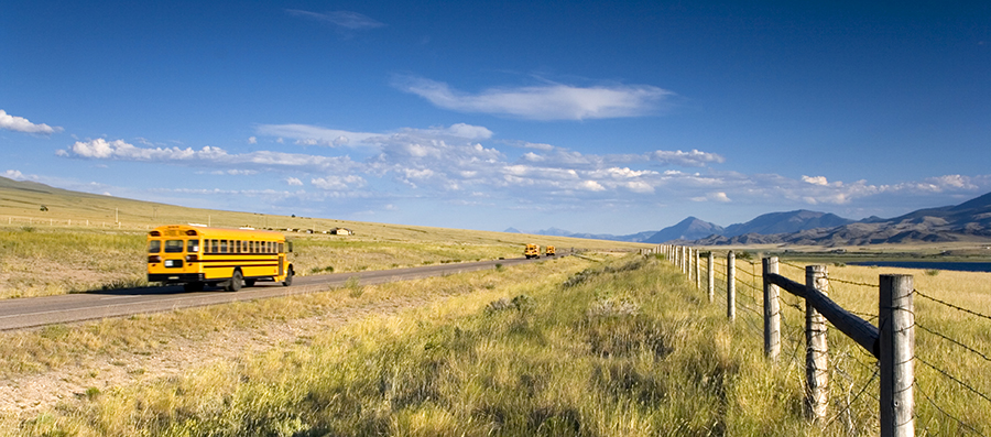 Image of a schoolbus driving through a rural area