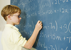 Boy doing math at chalkboard