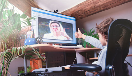 Image of young student giving thumbs up to teacher on screen