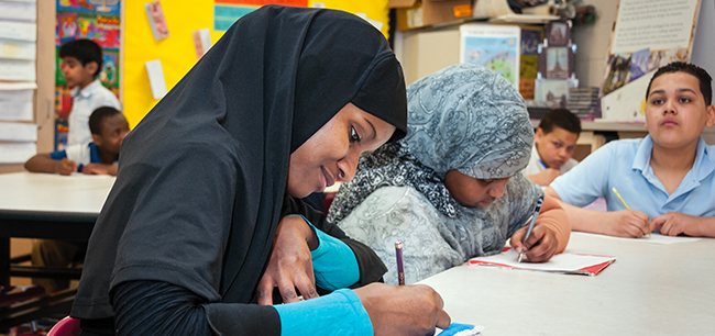 Cleveland students with hijabs writing at a table