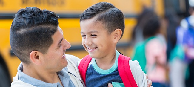 Image of father and son hugging in front of a schoolbus