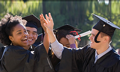 grads in cap and gown laughing