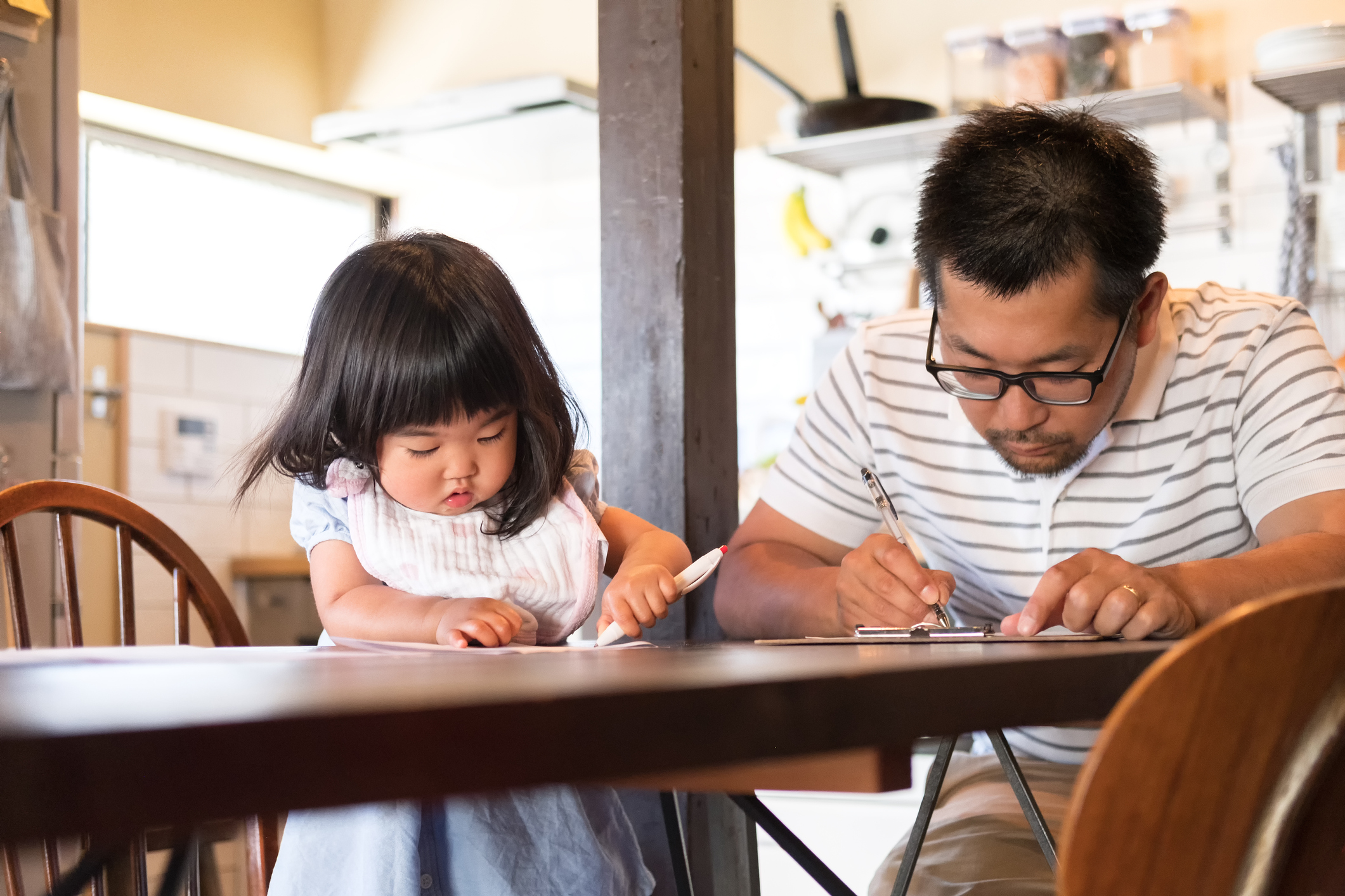 Father and daughter taking a survey at kitchen table