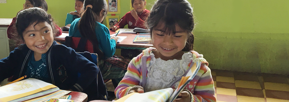 Image of two young girls reading in a Honduras classroom