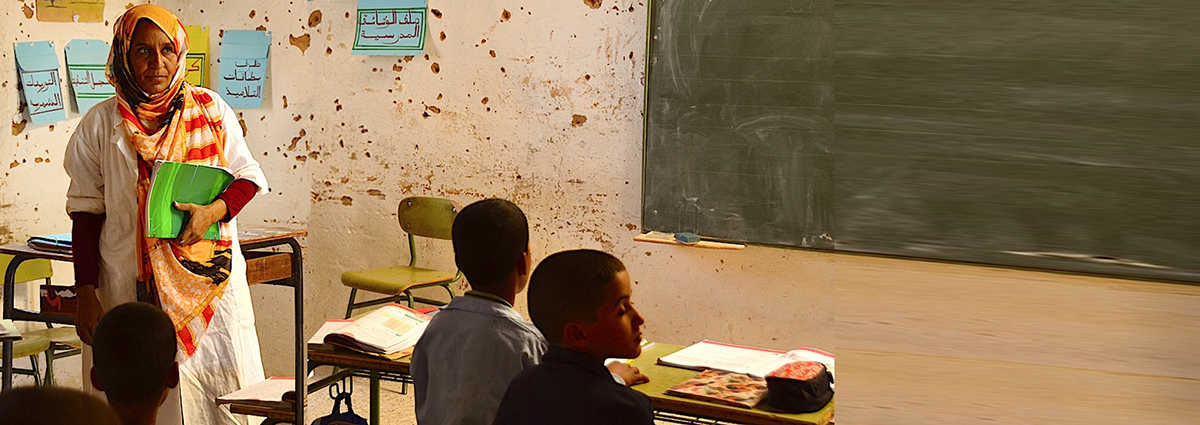 Image of teacher in a classroom with refugee students