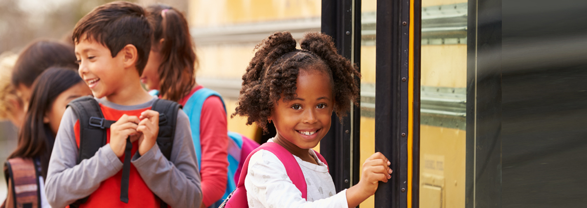 Image of young girl getting onto a school bus