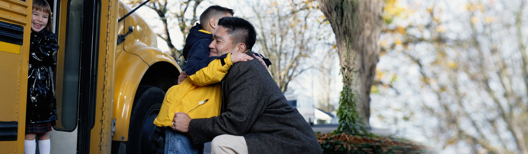 Parent hugging child by a school bus