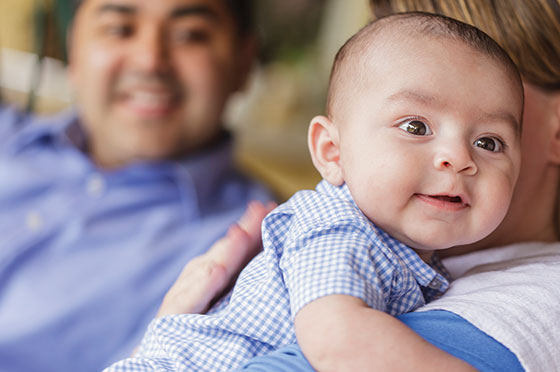 Image of baby in a gingham shirt being held by a parent