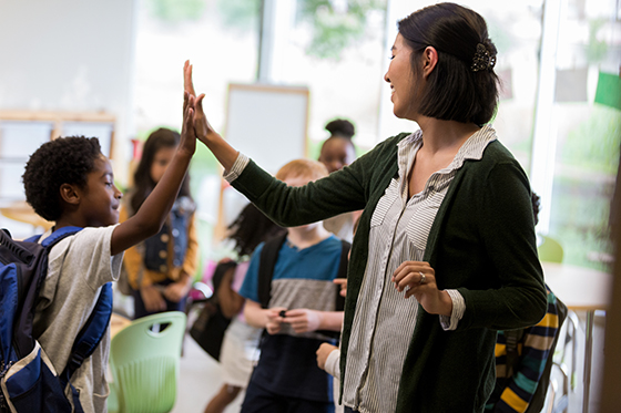 Image of teacher high-fiving a student