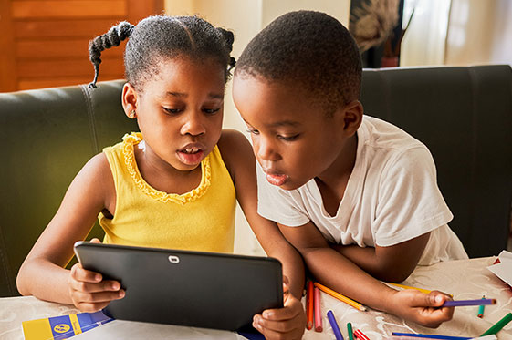 Image of young boy and girl looking at a tablet together