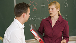Teachers conferring at chalkboard