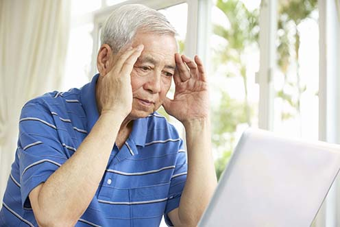 Image of confused older man at computer