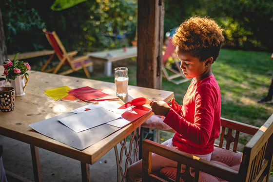 Image of elementary age child doing crafts outdoors