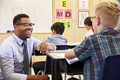 Image of smiling African American teacher with student