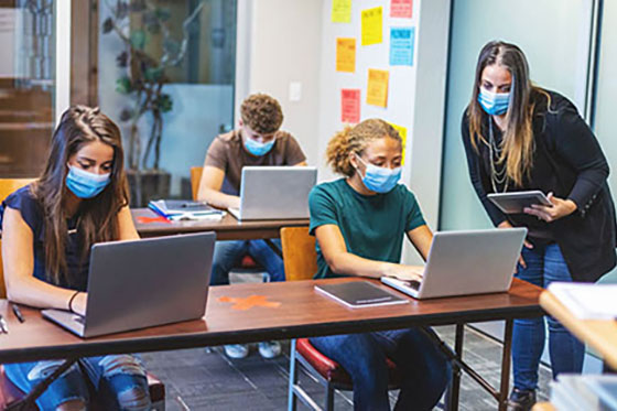 Image of students at computers with masks