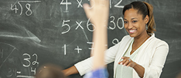 Image of teacher at chalkboard smiling at student raising hand