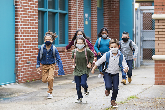 Image of kids running outside school, wearing masks