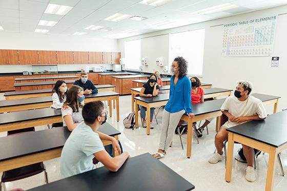 Image of socially distanced teachers in a classroom, wearing masks