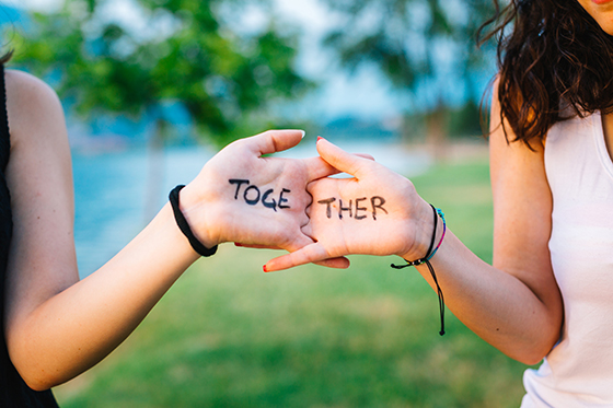 Image of hands with the word together written on them