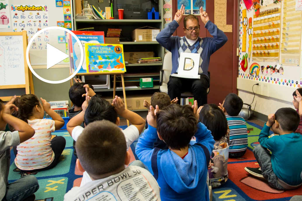 teacher reading to exuberant young students
