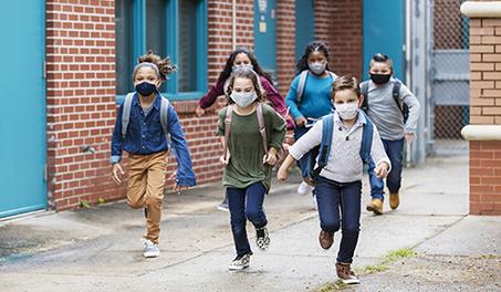 Image of kids running outside school, wearing masks