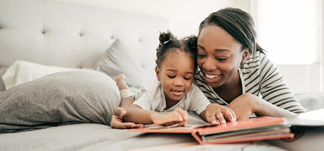 Image of mother with young girl reading on bed together