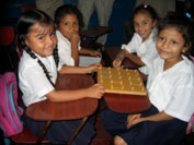 Picture of four young students at desks.