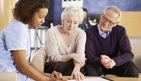 Image of older couple looking at papers with a health professional
