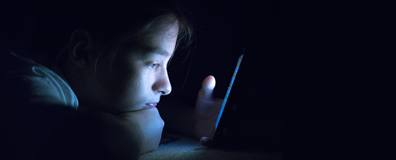 Image of young student looking at a computer screen in the dark
