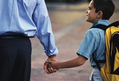 Image of boy with backpack holding his father's hand