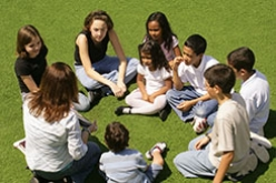 Image of kids in a circle with teacher outside after school