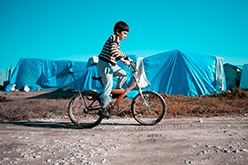 Image of Syrian boy riding a bicycle in a refugee camp
