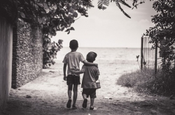 Image of two boys walking together, arm in arm