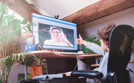 Image of child giving teacher on screen a thumbs up
