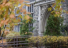 gothic college archway with fall leaves