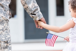 Image of girl with flag holding soldier's hand
