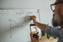 Image of man doing math on a whiteboard