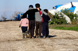 Image of children walking arm-in-arm in a refugee camp