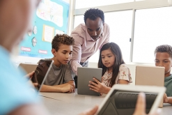 Image of teacher in classroom with students on tablets