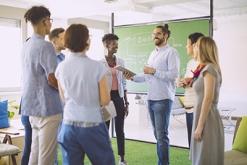 Teachers standing by chalkboard talking